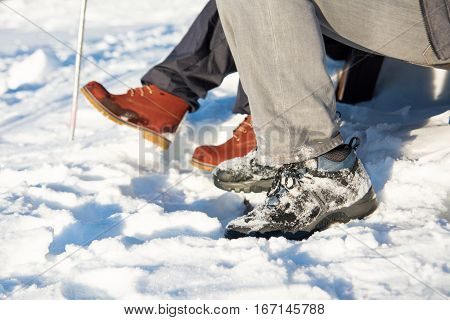 Snow Covered Boots And Hiking Stick