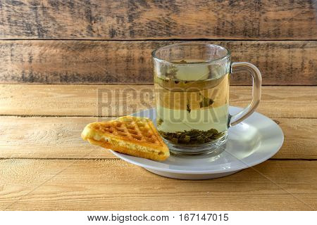 Green tea in a transparent mug with waffle on a wooden background