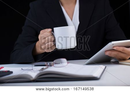 A corperate business woman holding a white cup of coffee reading from the iPad on the other hand on her working desk.