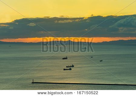 Sunset over seacoast with transport ship in the ocean seascape background
