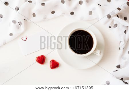 Romantic love background - cup of coffee blank love card and two heart shaped candies flat lay. Love romantic concept.