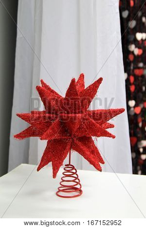 Pretty party favor of large red star set on table at celebration.