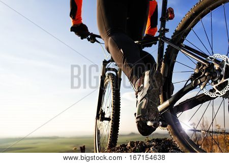Close-up view on a cyclist. Biker riding a bike on the mound view from below on a background of blue sky. Wide angle.
