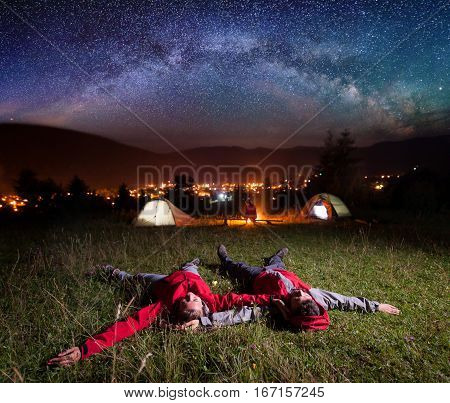 Loving Couple Admiring Bright Stars And Lying On The Grass