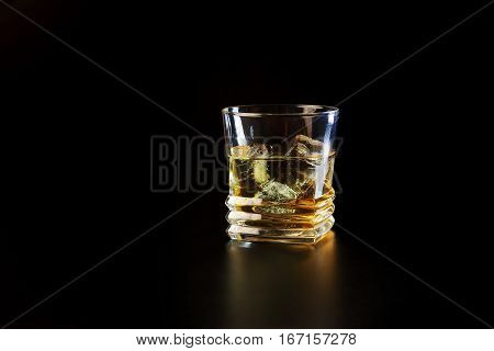 Glass of alcohol on a black table in the bar. Lonely scottish glass of whiskey with ice.