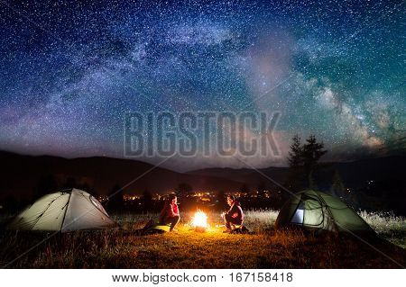Romantic Couple Sitting At Campfire Near Tents In The Night