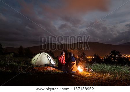 Night For Couple Of Sitting Face To Face Near Campfire