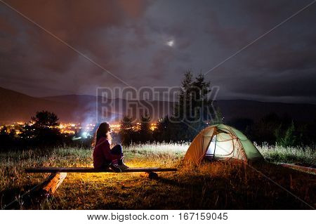 Thoughtful Girl Sitting On A Bench Near Tent And Campfire