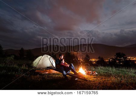 Camping Evening Couple Sitting On Boards Near Campfire