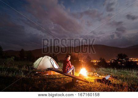Woman Enjoying A Bonfire Near Tent Under Cloudy Sky