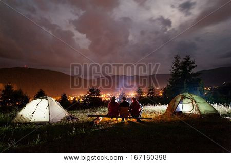 Three Tourists Sitting On Boards Around The Campfire Near Tents
