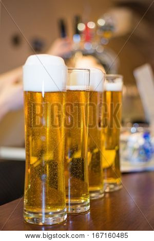 Barman pours foamy beer into a glass at the bar
