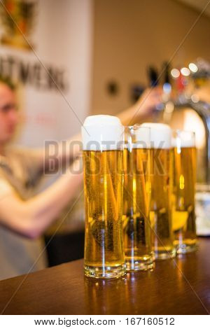 barman pours foamy beer in glasses with bubbles
