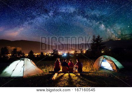 Friends Hikers Sitting Beside Camp And Tents In The Night
