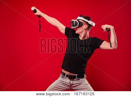 Joyful Guy Experiencing Virtual Reality Through A Vr Headset Isolated On Red Background