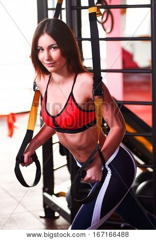 Girl With Long Brunet Hair Doing Exercises With Fitness Trx Expander In Gym