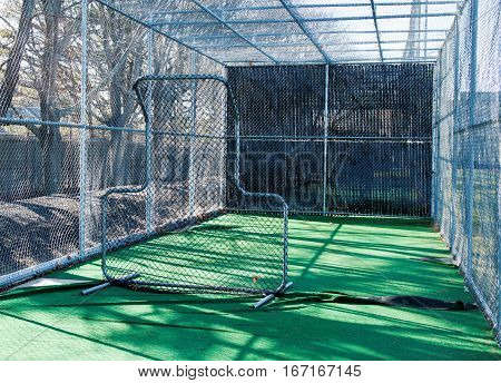 The view from inside a baseball batting cage from behind the pitching screen