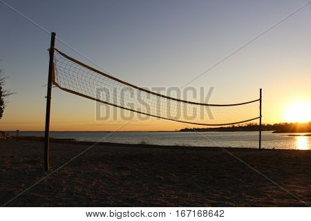 volleyball net silhouetted on beach at sunset with the ocean behind.