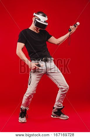 Male Immersed In Interactive Virtual Reality Video Game Doing Gestures On Red Background. He Is Wear