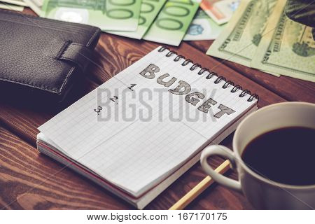 Budget planing concept. Notepad with word Budget, mobile phone, cup of coffee, pouch and money on wooden background. Vintage toned picture.