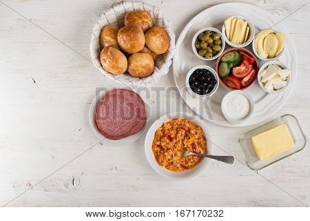 Traditional Turkish breakfast top view: cooked egg menemen pogaca pasties vegetables cheeses olives and halal turkey salami selective focus; copy space for text