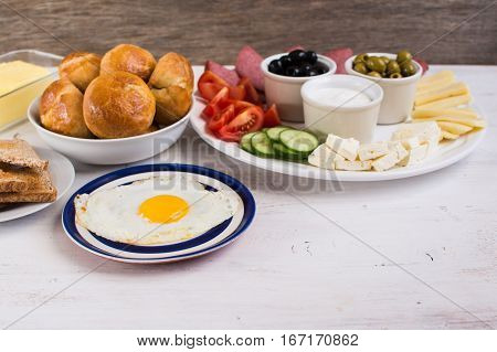 Traditional Turkish breakfast: egg toast pogaca pasties vegetables cheeses olives and halal turkey salami selective focus; copy space for text