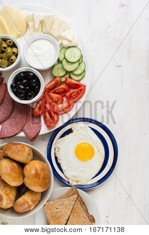 Traditional Turkish breakfast top view: egg toast pogaca pasties vegetables cheeses olives and halal turkey salami selective focus; copy space for text
