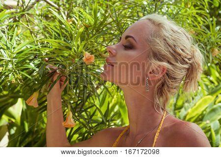 Sensual blond woman wearing crochet bikini smelling flower over tropical plants background