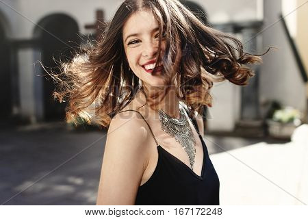 Happy Stylish Woman Waving Hair In Sunlight At Old European City Street, Luxury Look, Space For Text