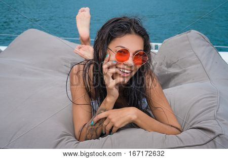 Young brunette woman in white swimsuit and sunglasses looking at the camera and smiling while  laying down on her stomach on the yacht at sunny summer day over beautiful turquoise sea background