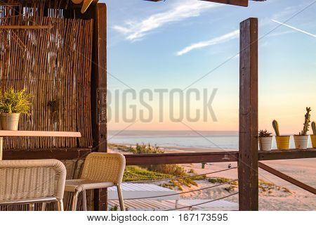 Beautiful sunset at the beach during a winter evening seen by the beach bar made interely of wood with a very rustic aspect.