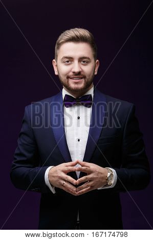 Handsome smiling man in tuxedo and bow tie looking at camera. Fashionable and festive clothing. emcee on dark purple background