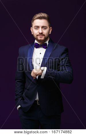 Handsome man in tuxedo and bow tie looks at his watch. Fashionable and festive clothing. emcee on dark purple background