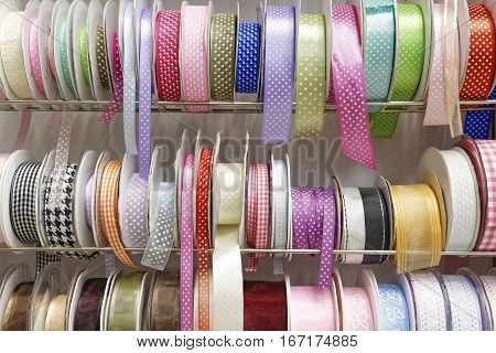 various colorful gift ribbon rolls on rack