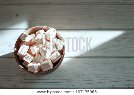 Marshmellow in a bowl on a wooden background. Top view. The concept of food.