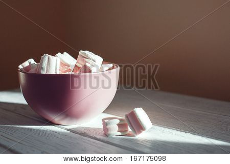Marshmellow in a bowl on a white table. The concept of food.