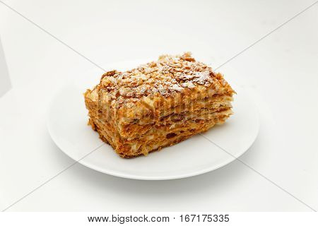 French Napoleon Cake of puff pastry with sour cream on a white plate close-up. Nutritious dessert. Selected Focus.