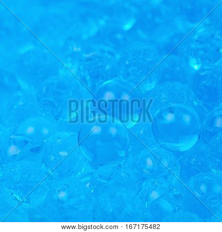 Surface coated with the multiple blue soil water beads as an abstract background composition with shallow depth of field