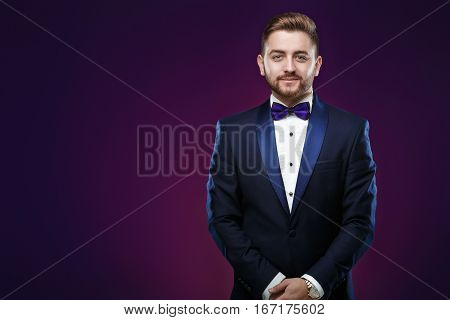 Handsome young man in tuxedo and bow tie looking at camera. Fashionable and festive clothing. emcee on dark purple background