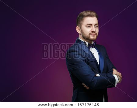 Handsome young man in tuxedo and bow tie looking at camera. Fashionable and festive clothing. Space for text