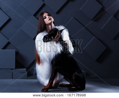 neautiful fashion woman with long hair sitting with black doberman dog on black background. She is wearing white white fur jacket
