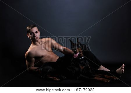 muscular man with a naked torso lying with black doberman dog on black background
