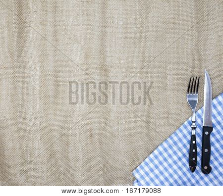 Canvas tablecloth, fork, knife for steaks and napkin. Is used to create a menu for a steak house. The background for the menu.