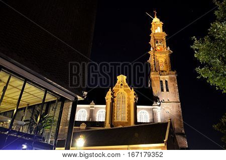Historic church with a clock tower at night in Amsterdam