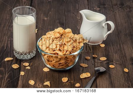 Healthy vegetarian breakfast, corn flakes, milk glass, milk jug and spoon on rustic dark wooden table, low key
