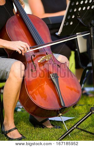 A woman playing a cello during a concert
