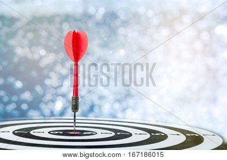 Close up shot red dart arrow on center of dartboard over bokeh background metaphor to target success