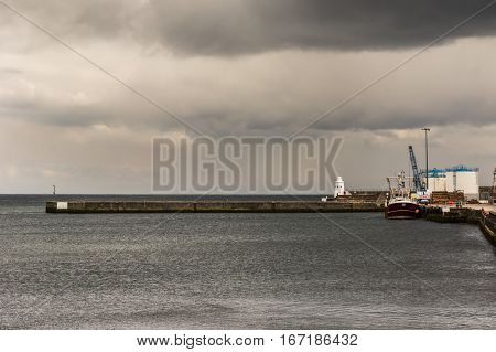 Wick Scotland - June 4 2012: The brown stone pier protrudes into Wick bay and protects the harbor of Wick. Fishing vessel and white fuel storage tanks on gray dark North Sea water under dark storm skies.