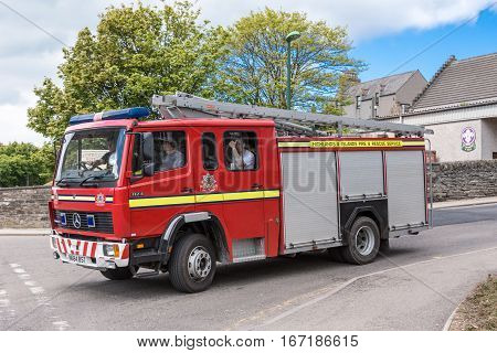 Wick Scotland - June 4 2012: Closeup of the local red fire truck on the move. Rescue personnel inside. Ladders on top. Street scene with tree and houses. Mercedes truck.