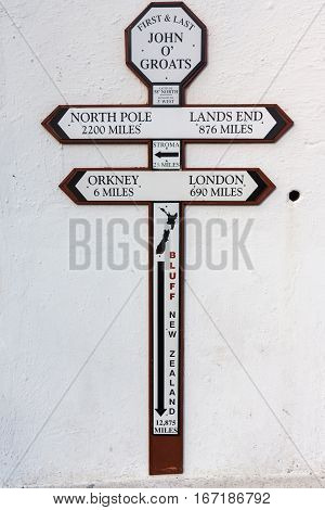John O Groats Scotland - June 5 2012: Cross sign with the distances to different spots on the globe. The town considers itself the north point of the British Island. Black and brown on white wall.